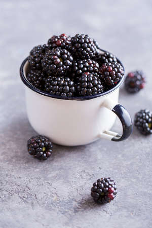 Juicy fresh blackberries in a cup. Organic healthy berries. Selective focus Imagens