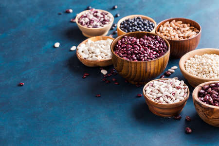 Assortment of beans on a blue background. Healthy food background wiht copy space.