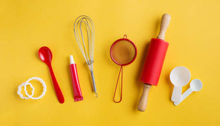 Different baking tools on yellow background, top view. Baking and cooking concept