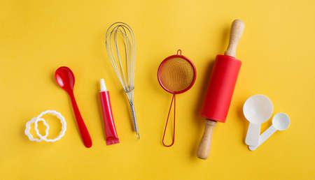 Verschiedene Backenwerkzeuge auf gelbem Hintergrund, Draufsicht. Back- und Kochkonzept