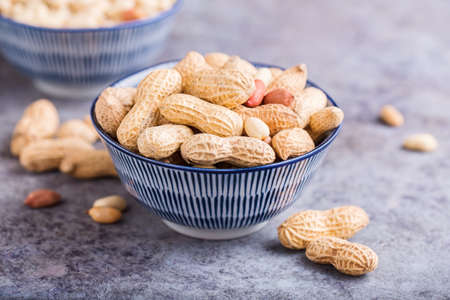 Peanuts in bowls close-up, selective focus.