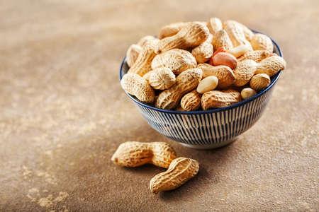 茶色の背景にボウルの生のピーナッツ 写真素材