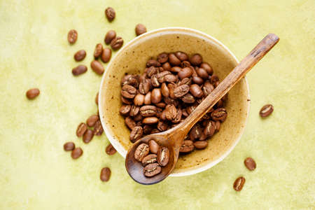 Fresh coffee beans in a bowl on a green background, top view. Selective focus, Фото со стока