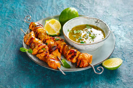 Chicken skewers with mint-lime dipping sauce. Shallow depth of field