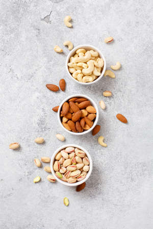 Organic nuts, almonds, cashew, pistachio in a bowls, delicious snack Top view