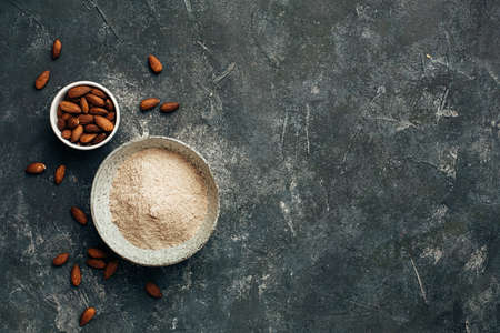 Bowl of almond flour and bowl of almonds from top view, copy space. Stok Fotoğraf