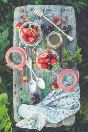 Summer breakfast. Yogurt with berries and fruits in glass jars, outdoors. Toned image. Top view.