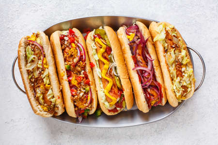 Hot dogs fully loaded with assorted toppings on a tray. Top view
