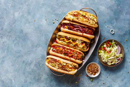 Different tasty hot dogs on a tray on a blue surface with copy space., top view.