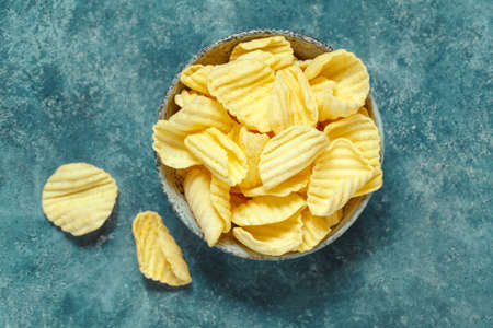 Crispy potato chips in bowl on a blue background. Stock Photo