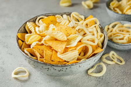 Crispy potato chips and onion rings and nachos in bowl