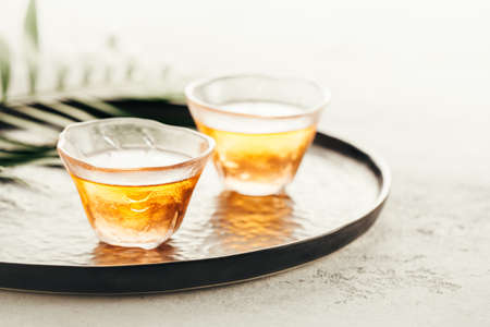 Two glass cups of freshly brewed tea on a tray