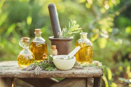 Verschiedene Massage- und Kosmetiköle in Glasflaschen aus Holz auf dem Tisch im Garten