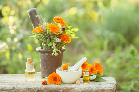 Variety of fresh herbs, calendula and oils for massage and aromatherapy. Selective focus.