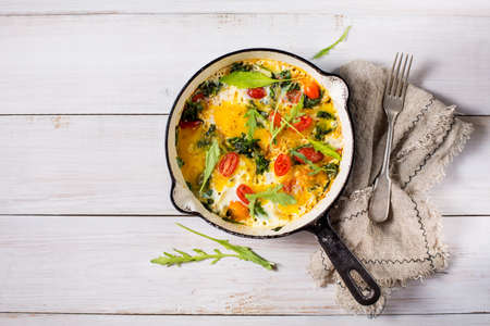 Fried eggs with spinach and tomatoes, top view. Food background with copy space. Stock Photo