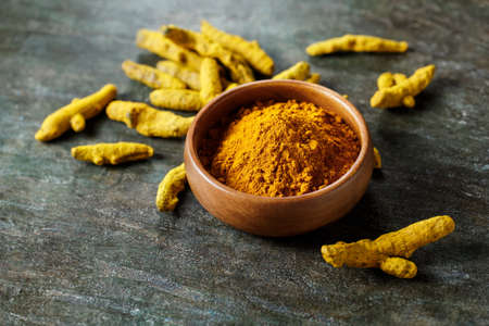 Turmeric powder in a bowl and turmeric root. Stock Photo