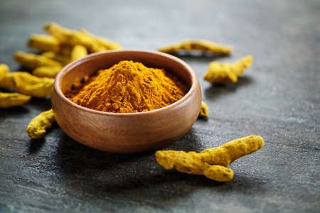 Turmeric in a bowl and curcuma root. Selective focus. Stock Photo