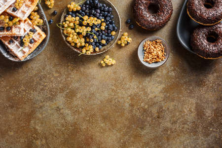Chocolate donuts and Belgian waffles. Food background with copy space. Top view. Stockfoto