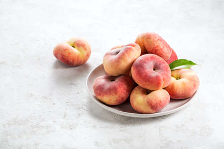 Ripe fig peaches on a plate. Food background with copy space.