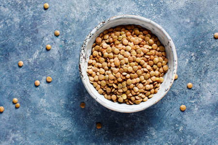 Lentils in a bowl, top view. Food background with copy space.