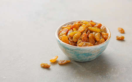 Golden raisins in a bowl. Food background with copy space. 免版税图像