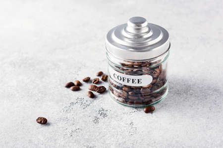 Glass jar with coffee beans on a gray textured background.
