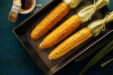 Fresh corn cobs on a baking tray with oil and spices. Natural products, healthy food.