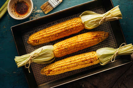 Sweet corn cobs on a baking tray with oil and spices. Top view.
