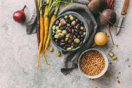 Organic broad beans, lentils and farm vegetables on a grey background. Ingredients for cooking. Selective focus Stok Fotoğraf
