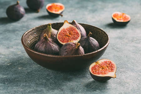 Organic figs and cut figs in a bowl. Selective focus on the top figs slice in the bowl.