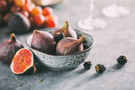 Organic raw figs with blackberries in a bowl. Foto de archivo