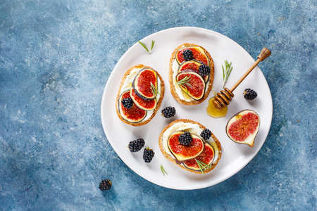 Top view of sandwich with soft cheese, fresh figs, blackberries and honey on white plate and blue background with copy space.