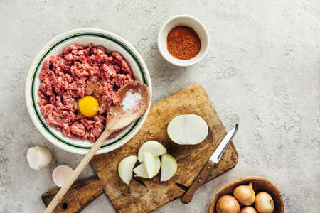 Fresh raw minced beef in a bowl with ingredients for cooking on a black kitchen table. Minced meat. Top view. Stock Photo