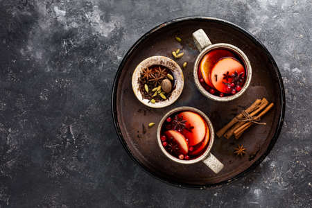Mulled wine in big rustic mugs with spices and apple fruit.