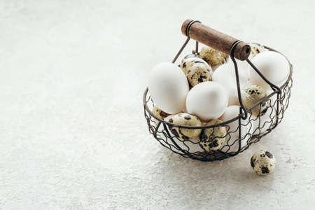 Fresh farm quail and chicken eggs in a basket. Stock Photo