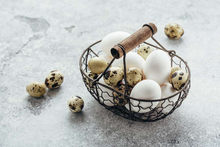 Quail and white chicken eggs in a basket.