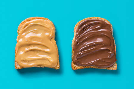 Two slices of toast with peanut butter and chocolate. Flat lay