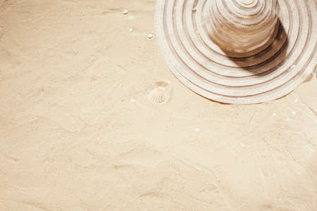White sun hat on the sand. Summer background with copy space and sand texture. Top view.