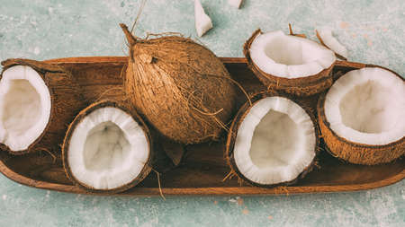 Fresh coconuts with coconut halves on a tray, close-up, top view. 写真素材