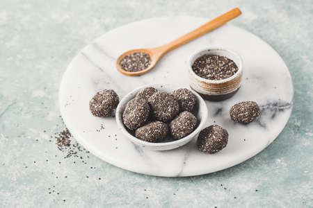 Healthy energy balls made from dried fruits covered with Chia seeds.