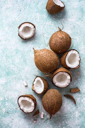 Fresh coconuts with coconut halves on a blue
