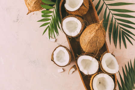 Fresh coconuts with coconut halves on a pink