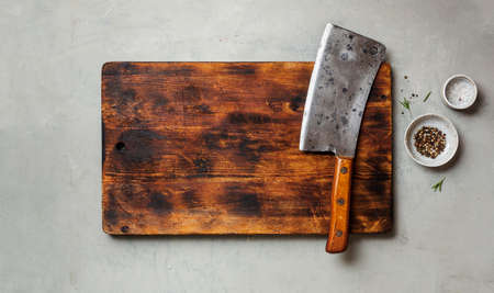 Vintage Meat cleaver on a empty old dark wooden cutting Board
