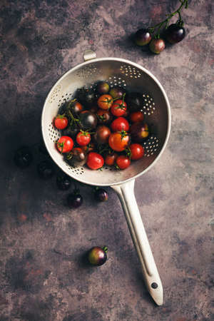 Black cherry tomatoes in a colander Stock Photo