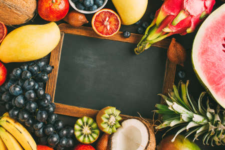 Exotic fruit and empty chalkboard with copy space. Top view. Thai fruits. Food background with copy space.
