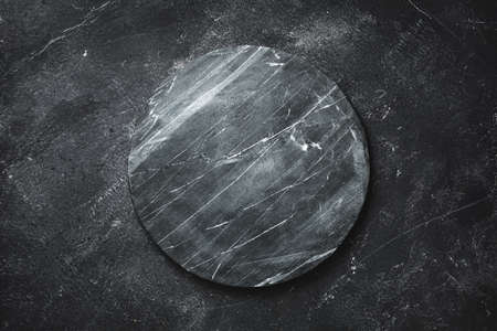 Round serving tray made of marble on a dark Reklamní fotografie