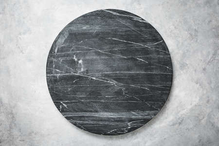 Round slab of black marble on a grey textured