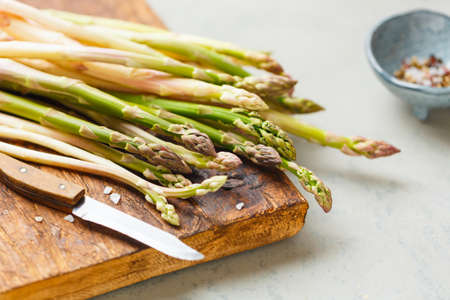 Freshly picked asparagus on a cutting Board, salt, pepper. The concept of healthy eating. Selective focus.
