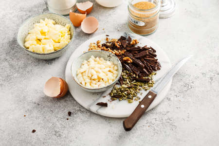 Baking tools and Ingredients for home Baking with Chocolate. Flour, sugar, eggs, butter and nuts. Stock Photo