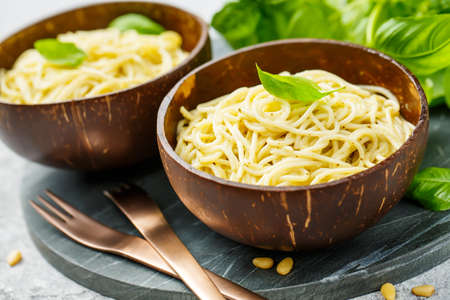 Delicious pasta with pesto sauce served in bowls of coconut. Close up.